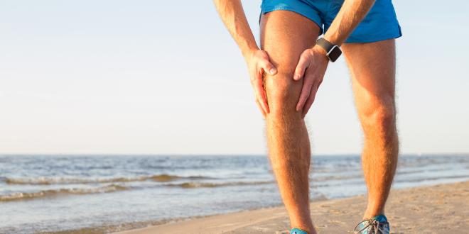 A man with an aching knee while running on the beach