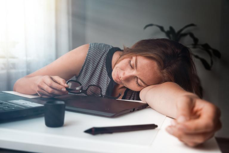 A young woman that has fallen asleep while working on her computer.